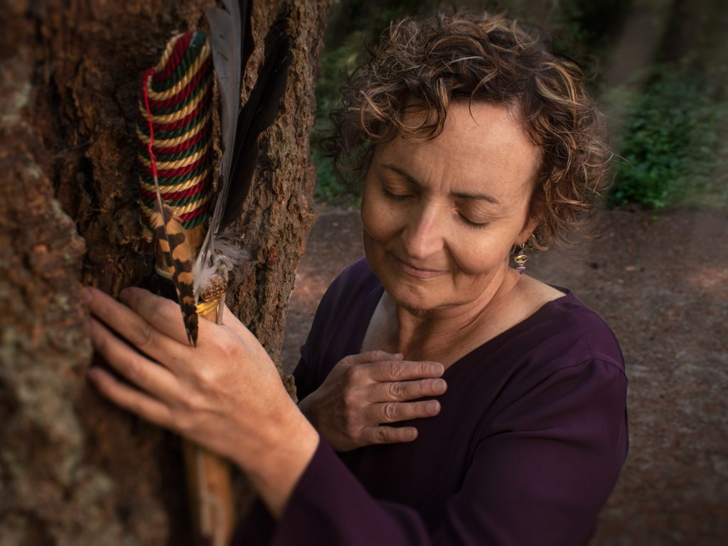Maureen in the forest, holding a feather. Her hand is on her heart.